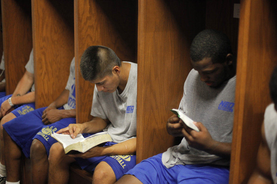 COLLEGE FOOTBALL: Wesley Satoe and Jevonte Cross read Bibles in the locker room after strength and conditioning training at Northeastern Oklahoma A&M College in Miami, Okla., Wednesday, July 18, 2012.  Photo by Garett Fisbeck, The Oklahoman