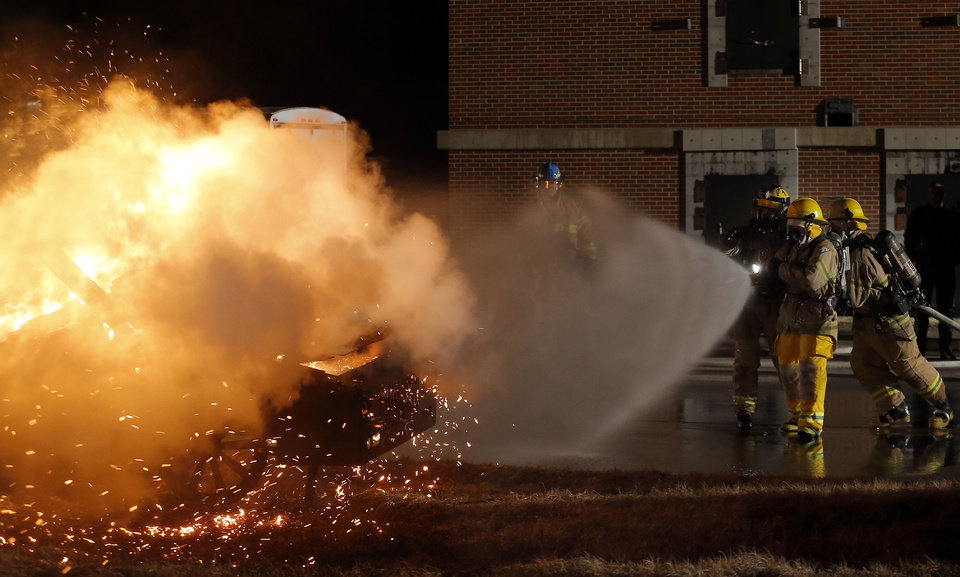 Photo - Students put out a car fire during Edmond Fire Department's Citizens Fire Academy. Photos9 by Sarah Phipps, The Oklahoman