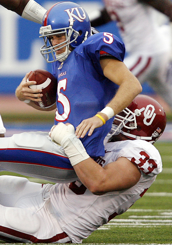 Photo - Oklahoma's Auston English (33) sacks Kansas quarterback Todd Reesing (5) during the second half of the college football game between the University of Oklahoma Sooners (OU) and the University of Kansas Jayhawks (KU) on Saturday, Oct. 24, 2009, in Lawrence, Kan. Oklahoma won the game 35-13. Photo by Chris Landsberger, The Oklahoman