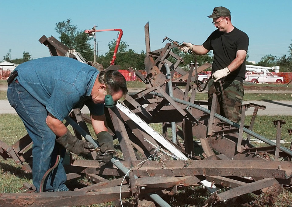 Tornado damage: Tinker Air Force Base.  Stacy Thomas of Mustang and Staff Sgt. Willard Rogers cutting up the twisted bleachers at Tinker's football field and running track located on the west side of the base. (Note: Thomas is civil employee and Rogers is military but both are with the civil engineers)