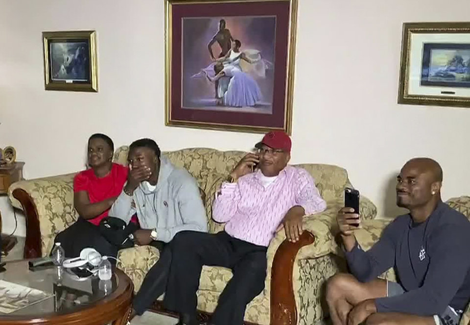 Photo - In this still image from video provided by the NFL, Kenneth Murray, second from left, watches the NFL football draft Thursday, April 23, 2020, in Missouri City, Texas. Murray was chosen by the Los Angeles Chargers. (NFL via AP)