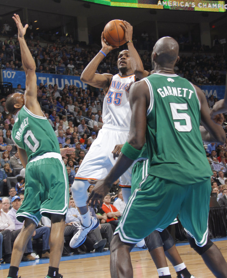 Photo - Oklahoma City Thunder small forward Kevin Durant (35) shoots the ball between Boston Celtics shooting guard Avery Bradley (0) and Boston Celtics power forward Kevin Garnett (5) during the NBA basketball game between the Oklahoma City Thunder and the Boston Celtics at the Chesapeake Energy Arena on Wednesday, Feb. 22, 2012 in Oklahoma City, Okla.  Photo by Chris Landsberger, The Oklahoman