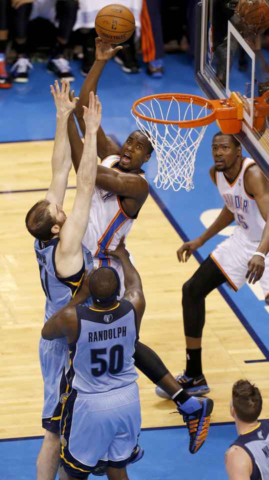 Photo - Oklahoma City's Serge Ibaka (9) shoots over Memphis' Kosta Koufos (41) and Zach Randolph (50) during Game 5 in the first round of the NBA playoffs between the Oklahoma City Thunder and the Memphis Grizzlies at Chesapeake Energy Arena in Oklahoma City, Tuesday, April 29, 2014. Photo by Nate Billings, The Oklahoman