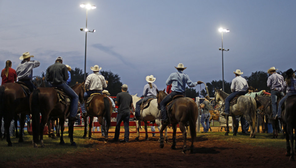 Photo - Contestants and rodeo workers watch the LibertyFest Rodeo as the sun sets in Edmond, Okla., Saturday, June, 23, 2013. Photo by Bryan Terry, The Oklahoman
