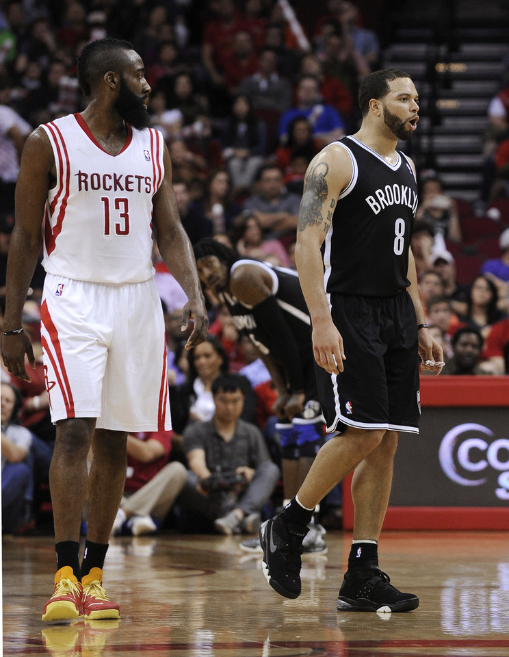 Brooklyn Nets' Deron Williams (8) reacts to being ejected from the game as Houston Rockets' James Harden (13) walks past during the fourth quarter of an NBA basketball game Saturday, Jan. 26, 2013, in Houston. The Rockets won 119-106. (AP Photo/Pat Sullivan)