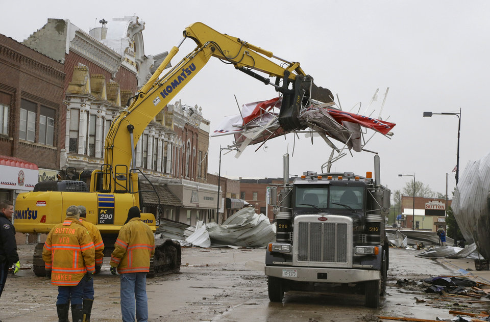 Photo - Debris is cleared from downtown Sutton, Neb., Monday, May 12, 2014, after a tornado touched down in town on Sunday. Several tornadoes moved across Nebraska on Sunday causing damage to homes and businesses in or near Sutton, Garland, Cordova and Daykin. The storms also left more than 18,000 utility customers without electricity. (AP Photo/Nati Harnik)
