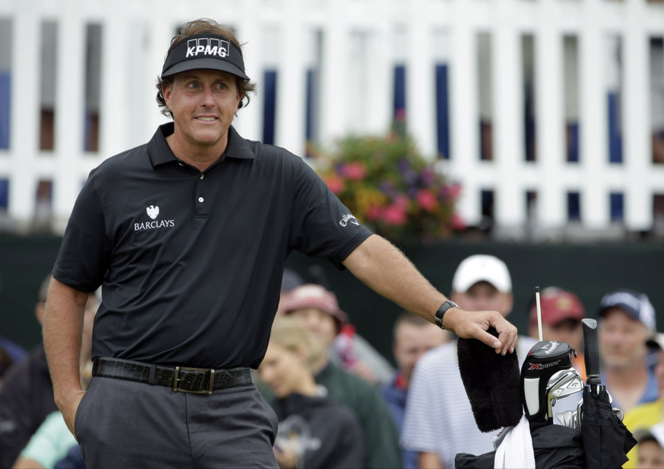 Photo - Phil Mickelson smiles as he waits for play to resume after a weather delay during the first round of the U.S. Open golf tournament at Merion Golf Club, Thursday, June 13, 2013, in Ardmore, Pa. (AP Photo/Charlie Riedel)