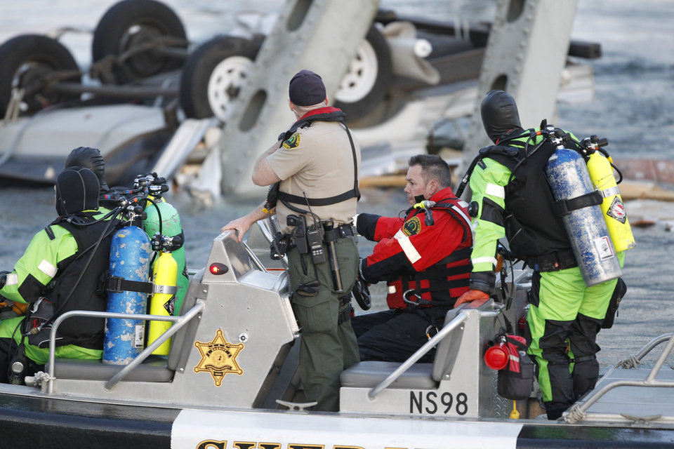 Photo - A rescue boat and divers search near a portion of the Interstate-5 bridge that is submerged after it collapsed into the Skagit river dumping vehicles and people into the water in Mount Vernon, Wash., Thursday, May 23, 2013 according to the Washington State Patrol. (AP Photo/Joe Nicholson)
