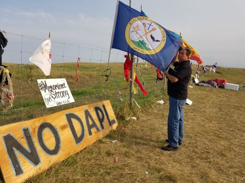Photo -  The Rev. David Wilson, superintendent of the Oklahoma Indian Missionary Conference of the United Methodist Church, holds one of the many tribal flags and banners posted near the Red Warrior prayer camp near the Standing Rock Sioux Tribe protests in North Dakota. [Photo provided]