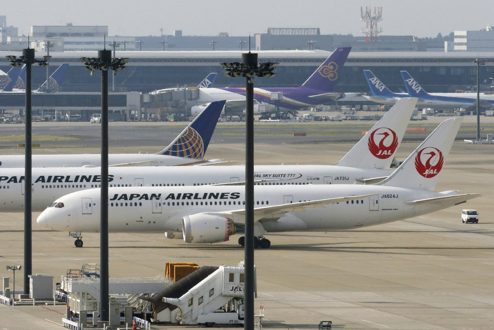 Photo - A Japan Airlines Boeing 787 plane, foreground, sits on a tarmac with others at Haneda Airport in Tokyo Friday, April 26, 2013. Japan's transport minister said Friday the government is poised to allow Japanese airlines to resume flying grounded Boeing 787s once they complete installation of systems to reduce fire risk in problematic lithium ion batteries. (AP Photo/Kyodo News) JAPAN OUT, MANDATORY CREDIT, NO SALES IN CHINA, HONG KONG, JAPAN, SOUTH KOREA AND FRANCE