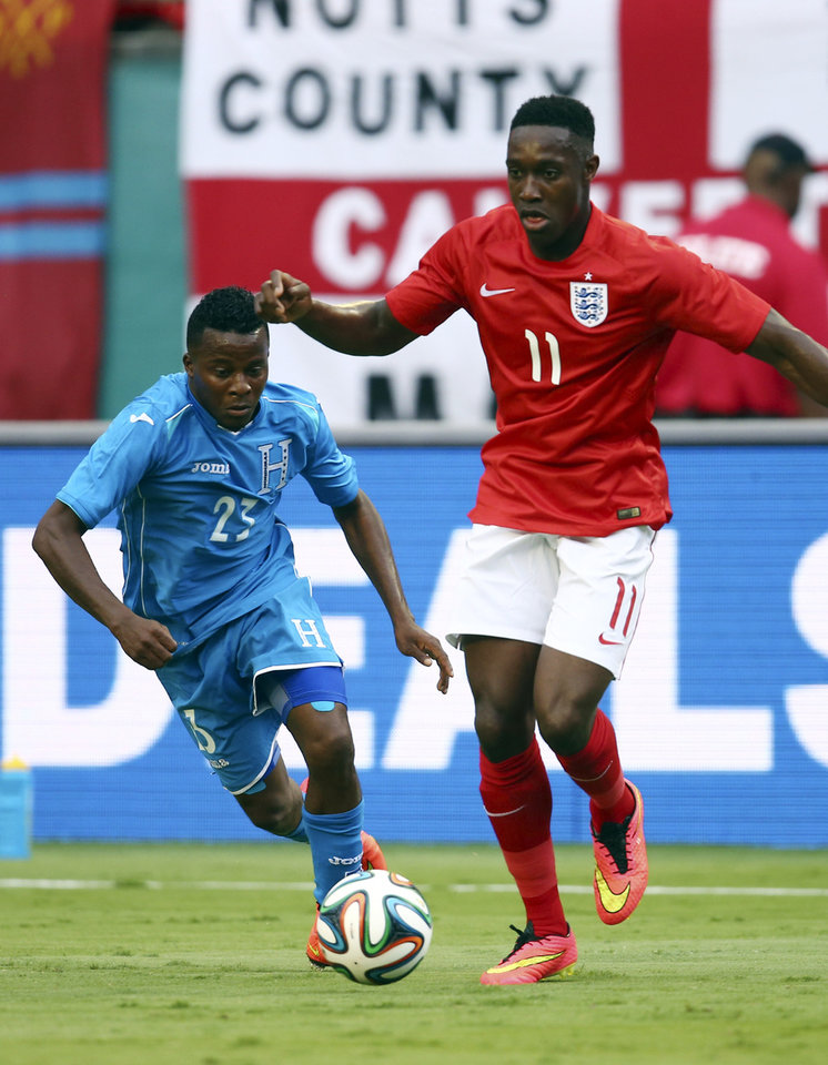 Photo - Englands' Danny Welbeck (11) dribbles the ball away from Honduras' Marvin Chavez (23) during the first half of a friendly soccer match in Miami Gardens, Fla., Saturday, June 7, 2014. ( AP Photo/J Pat Carter)