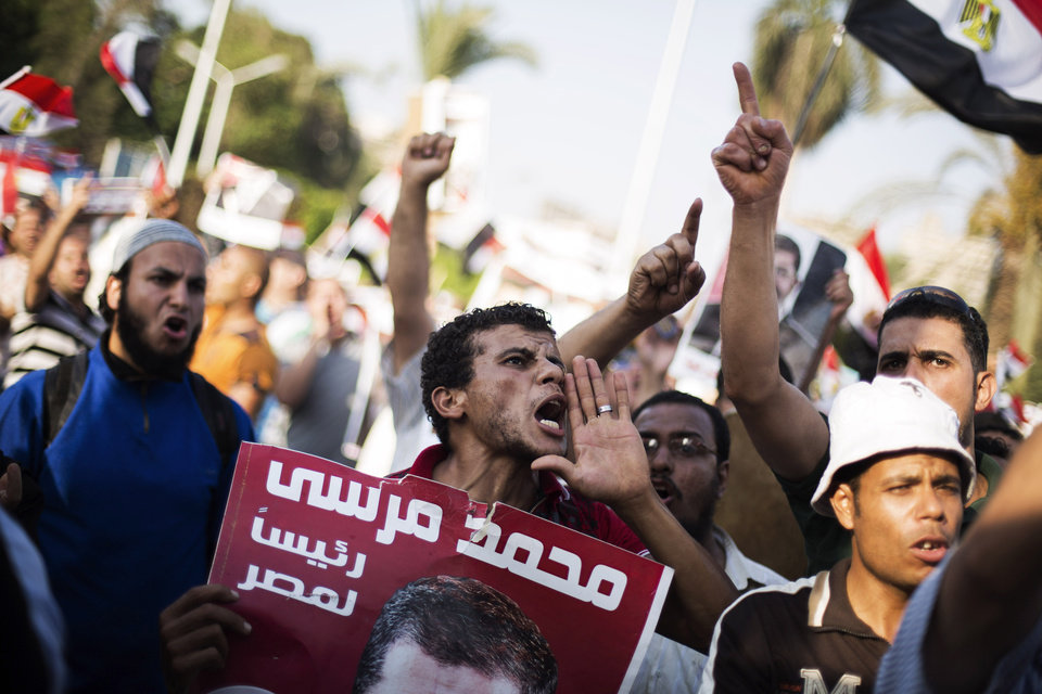 Supporters of Egypt's ousted Islamist President Mohammed Morsi chant slogans during a rally near the University of Cairo, Egypt, Thursday, July 4, 2013. After sweeping out Egypt�s Islamist president, the military moves swiftly against his Muslim Brotherhood, taking the dramatic step of arresting the group�s revered leader at a beachside villa and bringing him to Cairo by helicopter. The crackdown tests the new army-backed leadership�s promises to guide Egypt to democracy, raising the question of how to include the 83-year-old fundamentalist group, which was banned under authoritarian regimes, rose to power after the first revolution and now vows not to participate after being toppled in a wave of popular anger.(AP Photo/Manu Brabo)