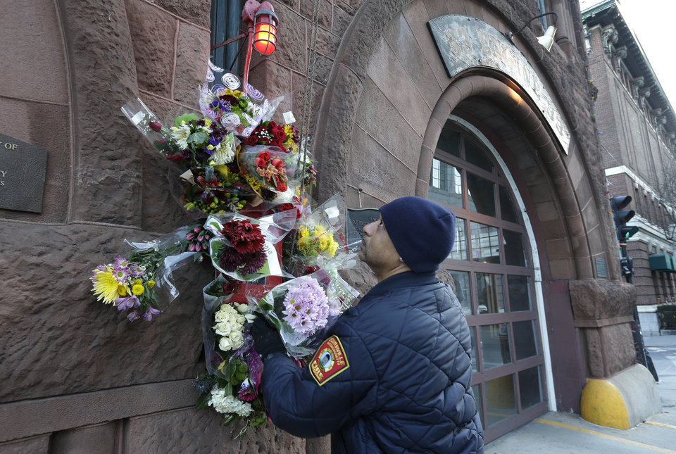 Photo - Somerville, Mass. firefighter Earl Johnson places flowers at a makeshift memorial on the front of fire station Engine 33, Thursday, March 27, 2014, in Boston. Fire station Engine 33 was the station of fallen firefighters Lt. Edward J. Walsh and Michael R. Kennedy who lost their lives fighting a 9-alarm fire in a four-story brownstone in Boston's Back Bay neighborhood Wednesday, March 26, 2014. (AP Photo/Steven Senne)