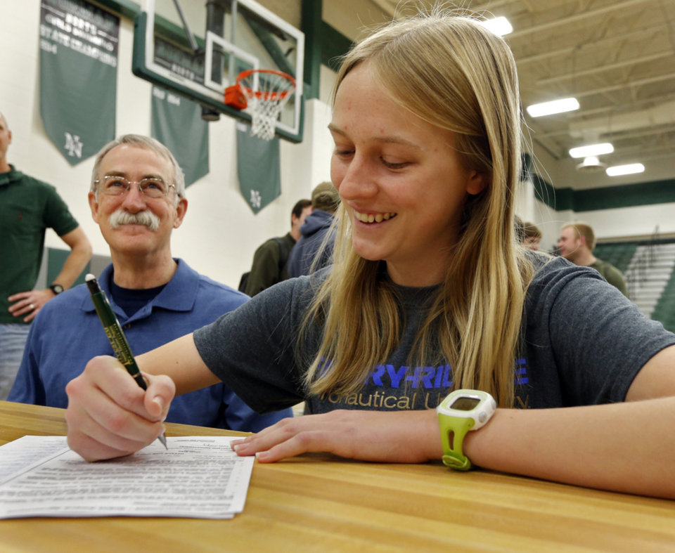 Photo - Rachel Chrisman signs a letter of intent to attend Embry-Riddle Aeronautical University in Prescott, AZ at Norman North High School on Wednesday, Feb. 4, 2015  in Norman, Okla. At left is her father Joe Crossman.  Photo by Steve Sisney, The Oklahoman