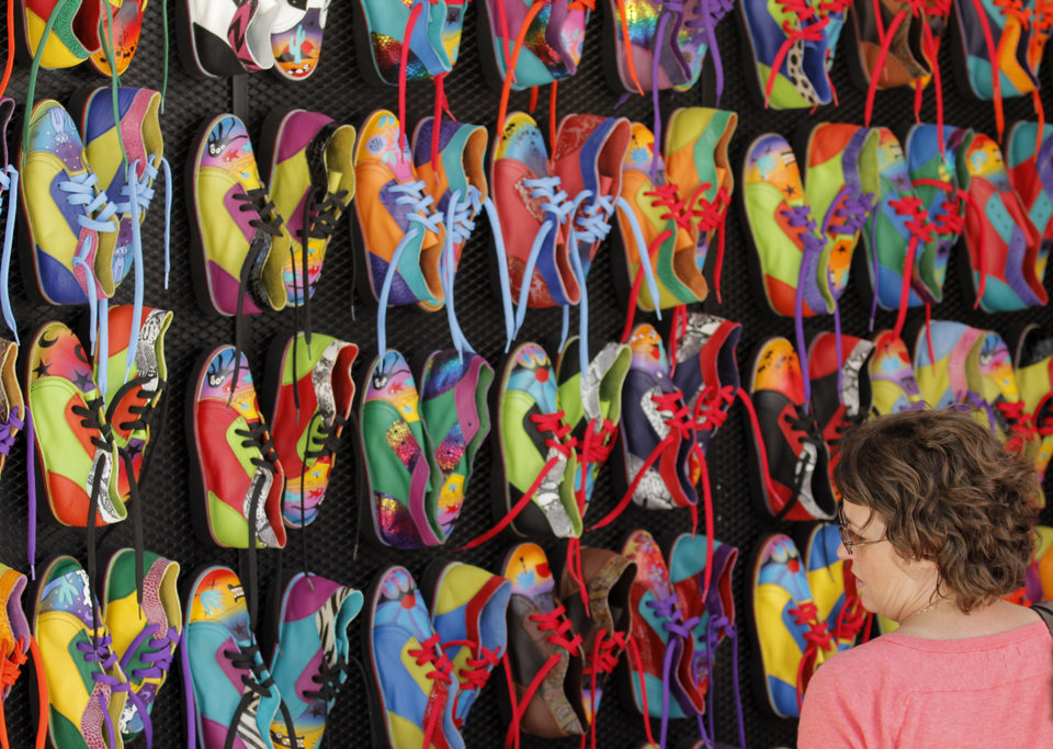 Photo - Paula Vallera, of Mustang, looks at the colorful shoes of artists Mark and Judy Carter from Prescott, Arizona during opening day of the Festival of the Arts in downtown Oklahoma City TUesday, April 24, 2012. Photo by Doug Hoke, The Oklahoman