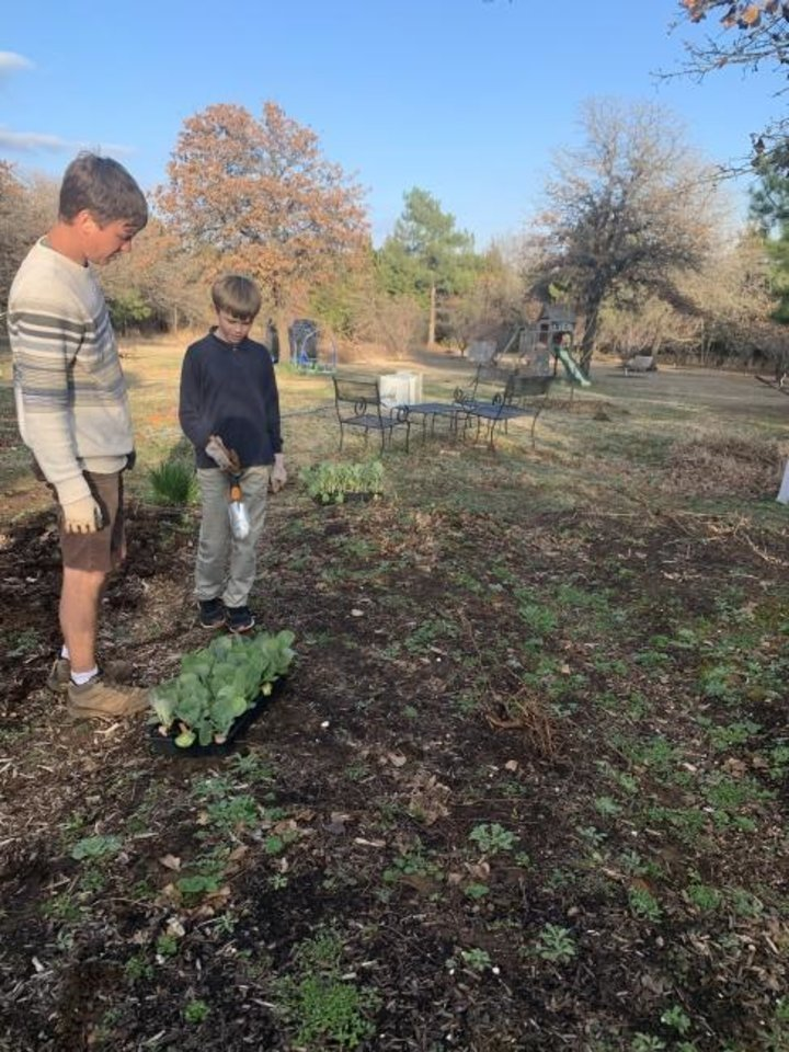 Photo -  Brandon Begley, owner of Dirt Therapy, and 11-year-old Ari Bytyqi plan an expansion of a vegetable garden in Spencer. [PROVIDED]