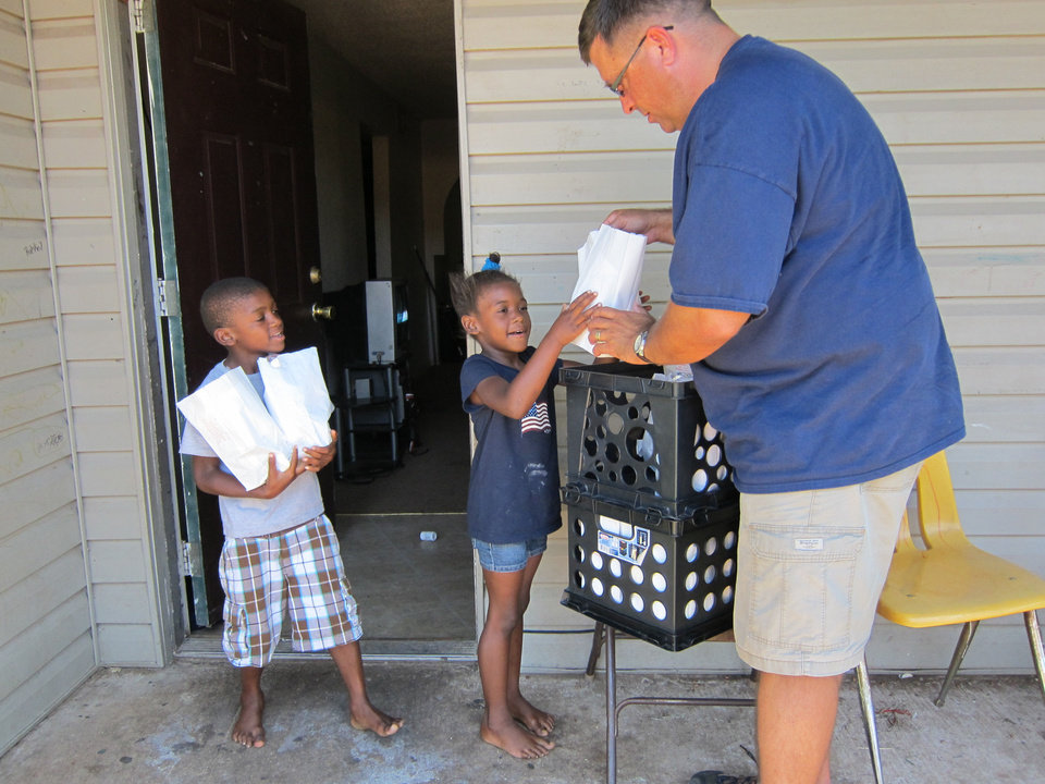 Photo - Children at the Wentwood at MacArthur Apartments choose lunches from the Rev. Chad Clement as part of the Truth Baptist Church summer meal outreach in west Oklahoma City.  Carla Hinton - The Oklahoman