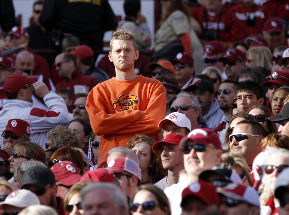 Photo - A Cowboy fan watches during the Bedlam college football game between the University of Oklahoma Sooners (OU) and the Oklahoma State University Cowboys (OSU) at Gaylord Family-Oklahoma Memorial Stadium in Norman, Okla., Saturday, Nov. 24, 2012. Photo by Steve Sisney, The Oklahoman