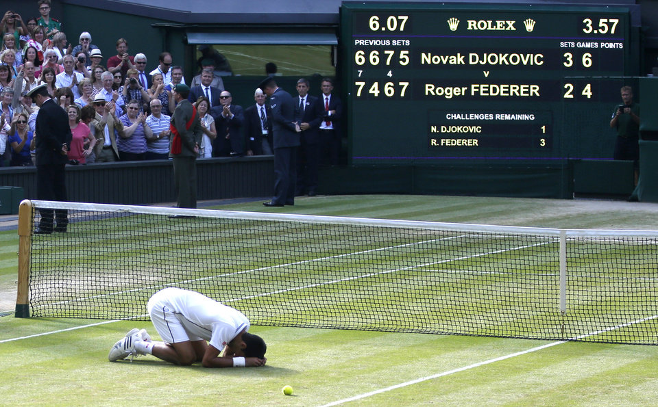 Photo - Novak Djokovic of Serbia places his head on centre court as he celebrates defeating Roger Federer of Switzerland in the men's singles final at the All England Lawn Tennis Championships in Wimbledon, London, Sunday July 6, 2014. (AP Photo/Pavel Golovkin)
