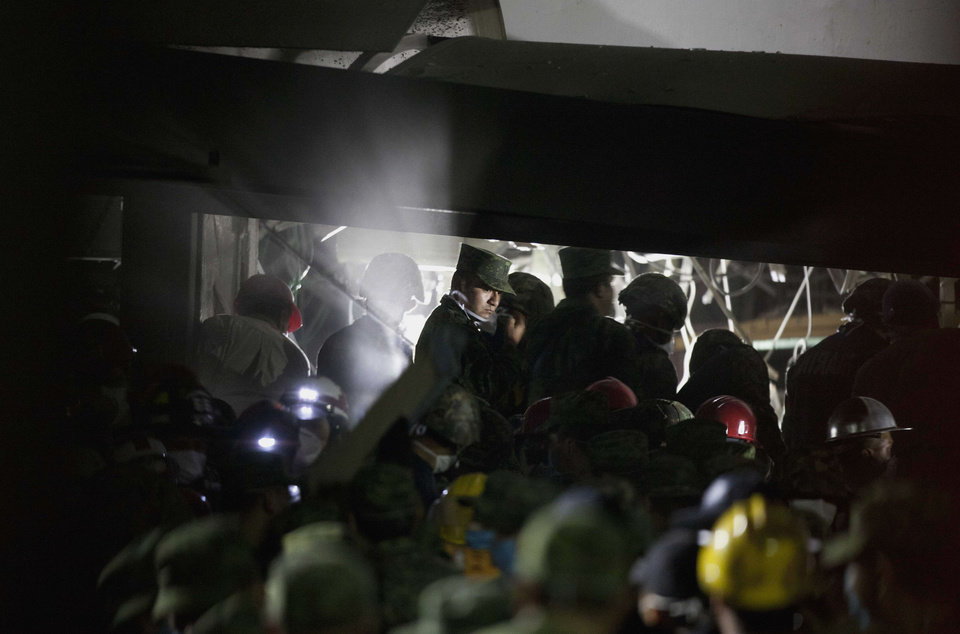 Photo - Rescue workers, firefighters and military search for survivors at the site of an explosion in a building at Mexico's state-owned oil company PEMEX complex, in Mexico City, Thursday Jan. 31, 2013. The explosion killed more than 10 people and injured some 80 as it heavily damaged three floors of the building. According to civil protection and local media some people remained trapped in the debris from the explosion, which occurred in the basement of an administrative building next to the iconic, 52-story tower of Petroleos Mexicanos, or PEMEX. (AP Photo/Eduardo Verdugo)