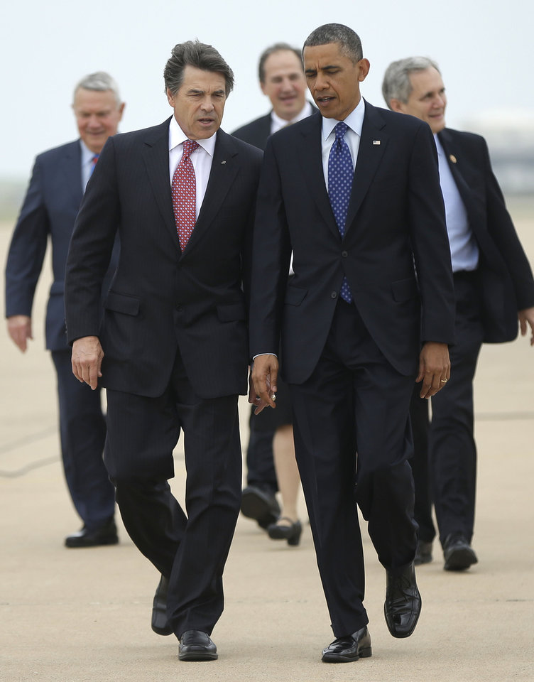 Photo - President Barack Obama, right, talks with Texas Gov. Rick Perry, left, as the walk on the tarmac during his arrival on Air Force One at Austin-Bergstrom International Airport, Thursday, May 9, 2013 in Austin, Texas. (AP Photo/Pablo Martinez Monsivais)