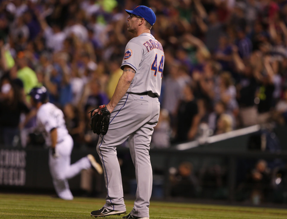 Photo - New York Mets relief pitcher Kyle Farnsworth, front, looks on as Colorado Rockies pinch-hitter Charlie Culberson circles the bases after hitting a two-run, walkoff home run in the ninth inning of the Rockies' 11-10 victory in a baseball game in Denver on Saturday, May 3, 2014. (AP Photo/David Zalubowski)