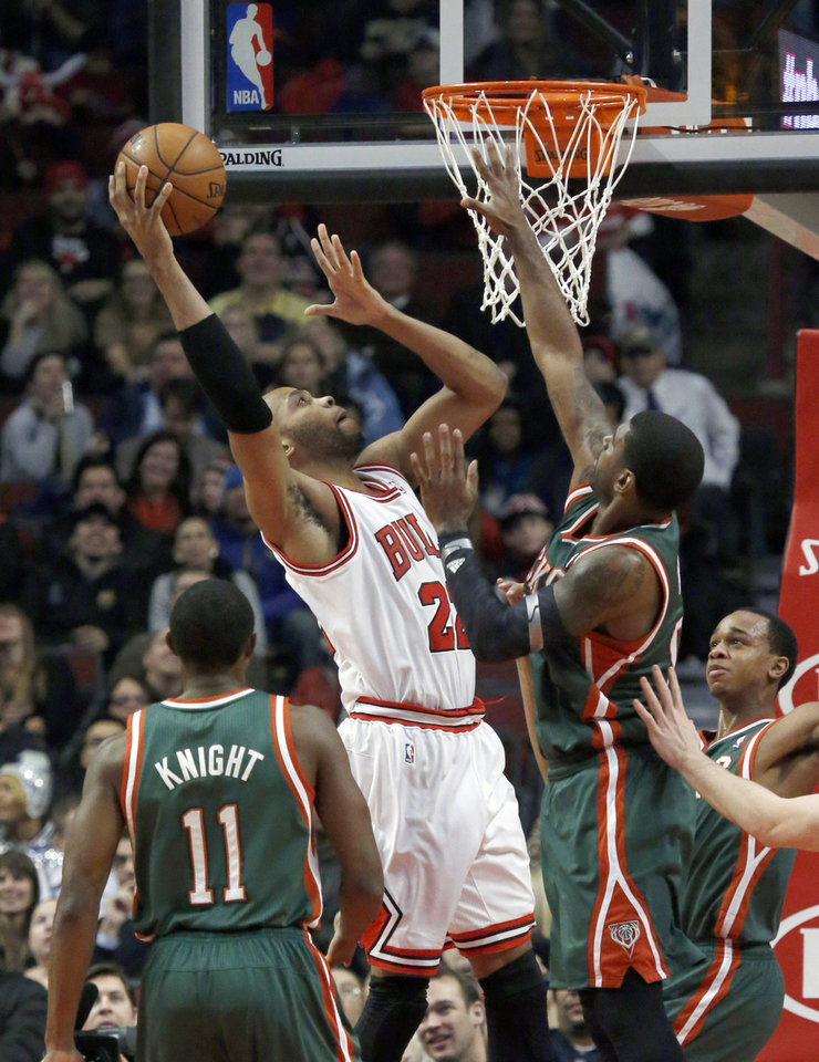 Chicago Bulls forward Taj Gibson (22) shoots over Milwaukee Bucks shooting guard O.J. Mayo, right, as Brandon Knight (11) watches during the first half of an NBA basketball game Tuesday, Dec. 10, 2013, in Chicago. (AP Photo/Charles Rex Arbogast)