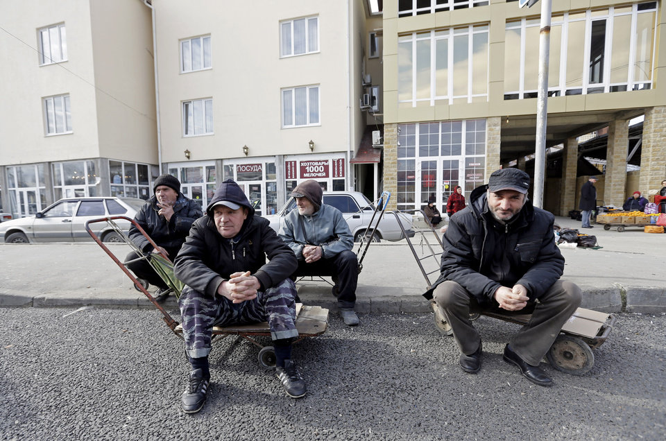 Photo - Men wait near the Abkhazian border Wednesday, Feb. 5, 2014, near Sochi, Russia. Abkhazia is a festering geopolitical sore, and the economic system still operating in these and many other parts of Russia is decidedly 19th century. As Russia opens its doors to a curious world with the Sochi Games, places like this border expose the vast contradictions still gripping the one-time superpower 21 years after the Soviet Union collapsed. (AP Photo/Morry Gash)