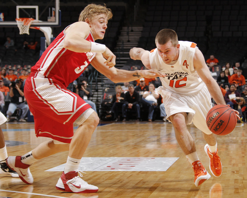 Photo - OSU's Keiton Page (12) tries to get past Hugh Greenwood (3) of UNM in the second half during the Bill Russell men's college basketball game of the Ramada All-College Classic between the Oklahoma State University Cowboys and the University of New Mexico Lobos at the Chesapeake Energy Arena in Oklahoma City, Sunday, Dec. 18, 2011. UNM beat OSU, 66-56. Photo by Nate Billings, The Oklahoman