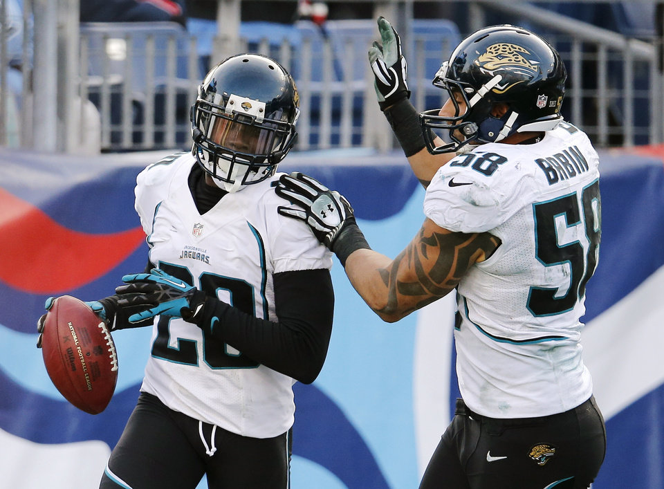 Photo - Jacksonville Jaguars cornerback Mike Harris (20) celebrates with defensive end Jason Babin (58) after scoring a touchdown after blocking a punt against the Tennessee Titans in the fourth quarter of an NFL football game, Sunday, Dec. 30, 2012, in Nashville, Tenn. The Titans won 38-20. (AP Photo/Joe Howell)