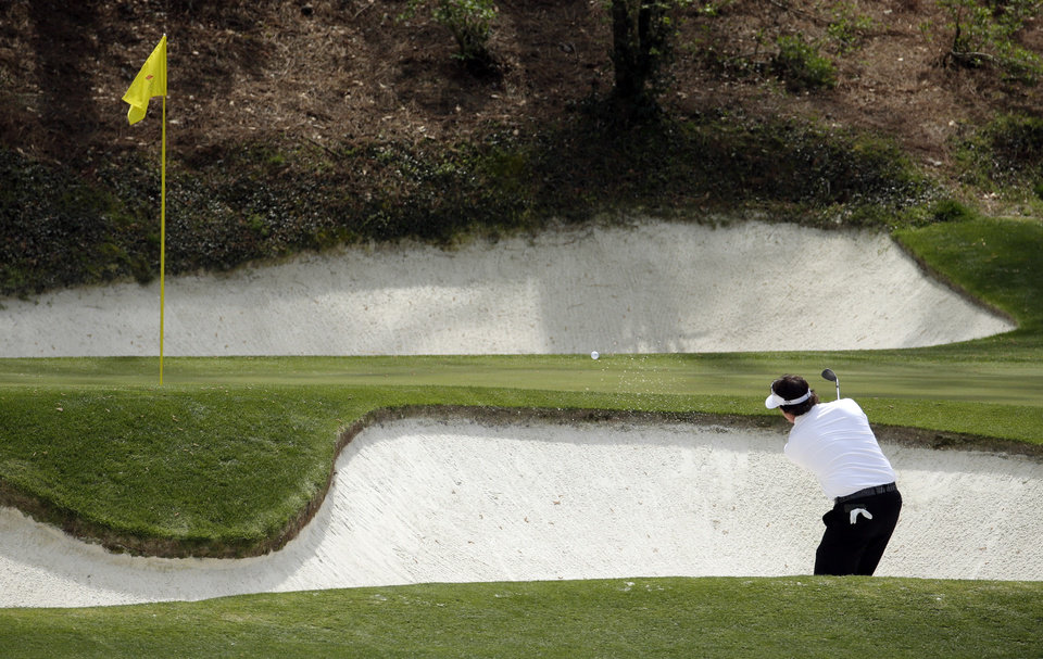 Photo - Phil Mickelson hits out of a bunker for the third  time on the 12th hole during the second round of the Masters golf tournament Friday, April 11, 2014, in Augusta, Ga. (AP Photo/Charlie Riedel)
