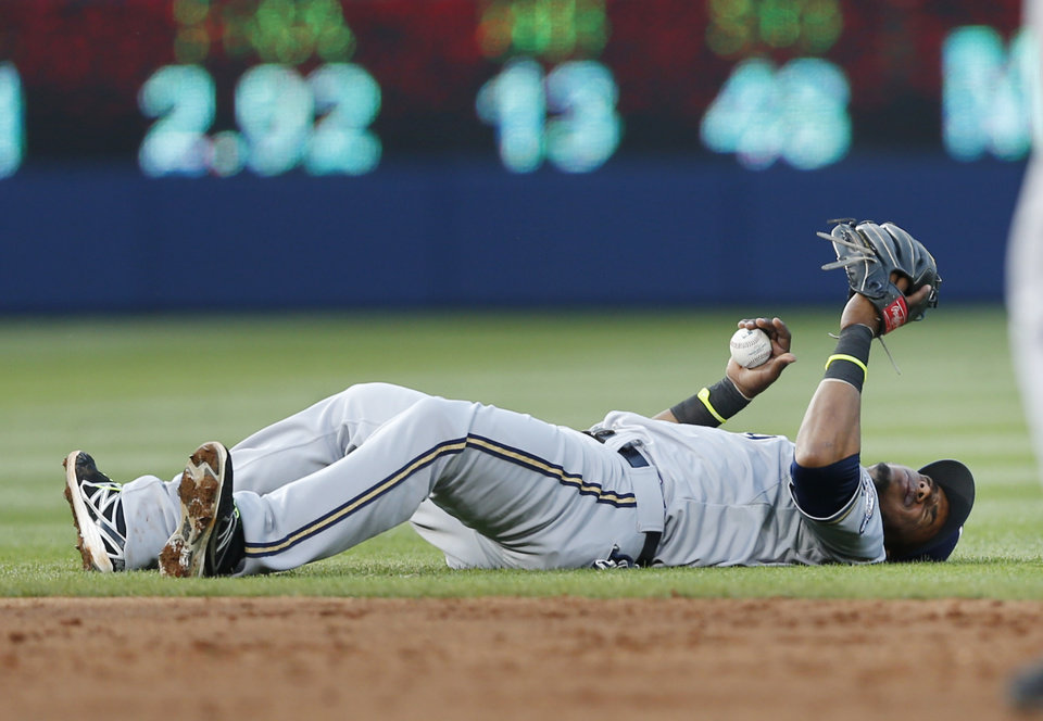 Photo - Milwaukee Brewers shortstop Jean Segura (9) lies on the field after being injured fielding a ball in the third inning of a baseball game against Atlanta Braves Wednesday, May 21, 2014 in Atlanta. Segura remained in the game. (AP Photo/John Bazemore)