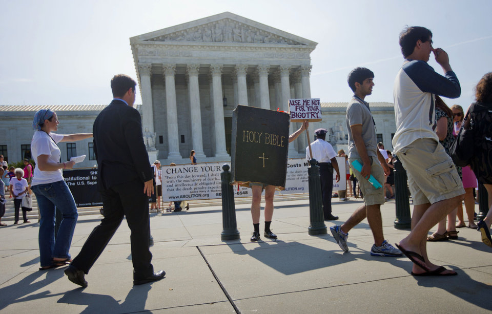 Photo - A demonstrator dressed as the 'Bible' stands outside the Supreme Court in Washington, Monday, June 30, 2014, awaiting the court's decision on the Hobby Lobby case. The Supreme Court says corporations can hold religious objections that allow them to opt out of the new health law requirement that they cover contraceptives for women.(AP Photo/Pablo Martinez Monsivais)