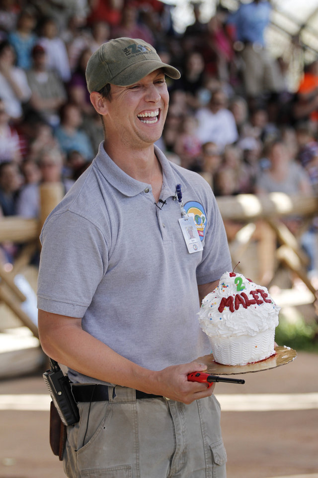 Nick Newby gets ready to light Malee's birthday candle during Malee's Second Birthday Bash at the Oklahoma City Zoo, Sunday, April 14, 2013.  Photo by Garett Fisbeck, For The Oklahoman
