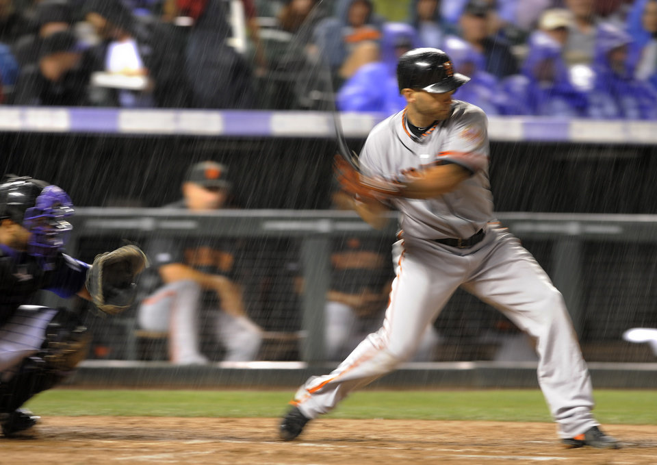 Photo -   San Francisco Giants' Marco Scutaro swings in a downpour of rain during the third inning of a baseball game Tuesday, Sept. 11, 2012, in Denver. (AP Photo/Jack Dempsey)