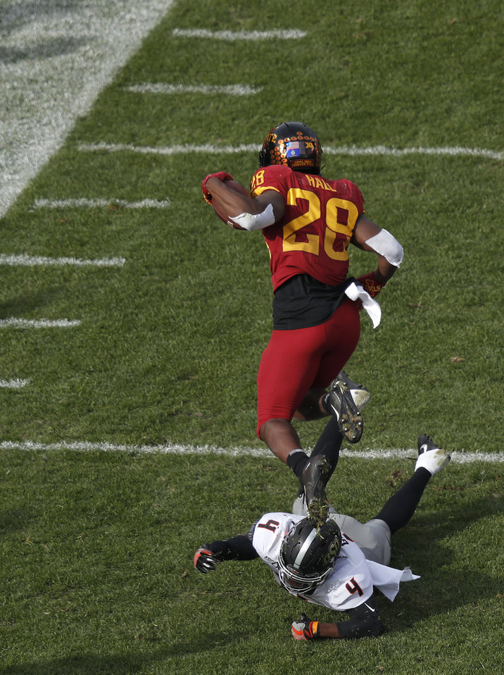 Photo - Oklahoma State cornerback A.J. Green, bottom, trips up Iowa State running back Breece Hall during the first half of an NCAA college football game, Saturday, Oct. 26, 2019, in Ames, Iowa. (AP Photo/Matthew Putney)