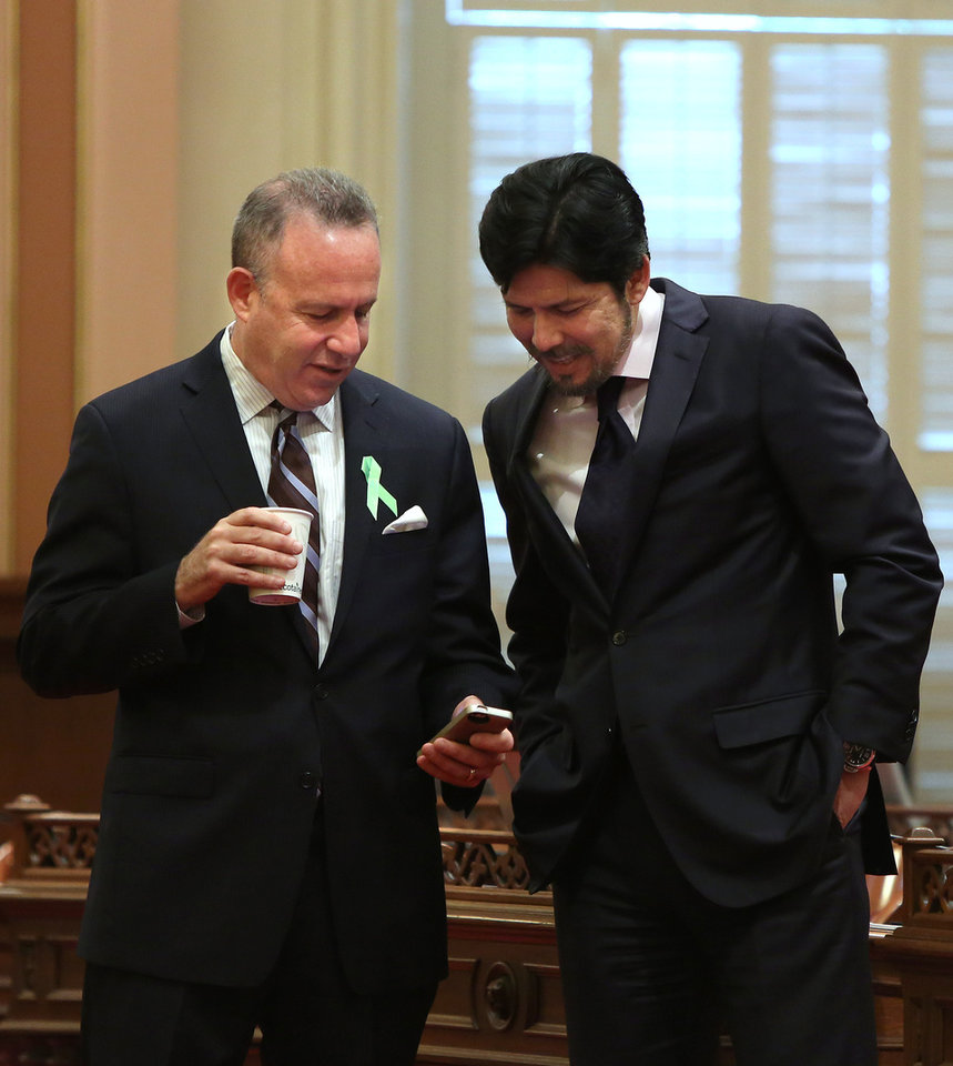 Photo - State Senate President Pro Tem Darrell Steinberg, D-Sacramento, left, and Sen. Kevin de Leon, D-Los Angeles look over Steinberg's smart phone as lawmakers debated a measure requiring electronics manufacturers to install a shut-off function on all smartphones manufactured and sold after July 2015,  at the Capitol  in Sacramento, Calif., Thursday May 8, 2014.  The bill, SB962 by Sen. Mark Leno, D-San Francisco, was approved by the Senate by a 26-8 vote.(AP Photo/Rich Pedroncelli)  in Sacramento, Calif., Thursday May 8, 2014.  (AP Photo/Rich Pedroncelli)