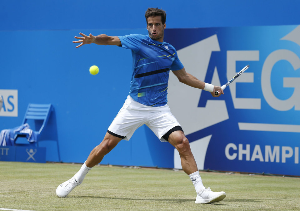 Photo - Spain's Feliciano Lopez plays a return to Australia's Lleyton Hewitt at The Queen's Club, grass-court tournament  in London Wednesday June 11, 2014. Lopez won the match 6-3, 6-4.  (AP Photo/Jonathan Brady/PA) UNITED KINGDOM OUT