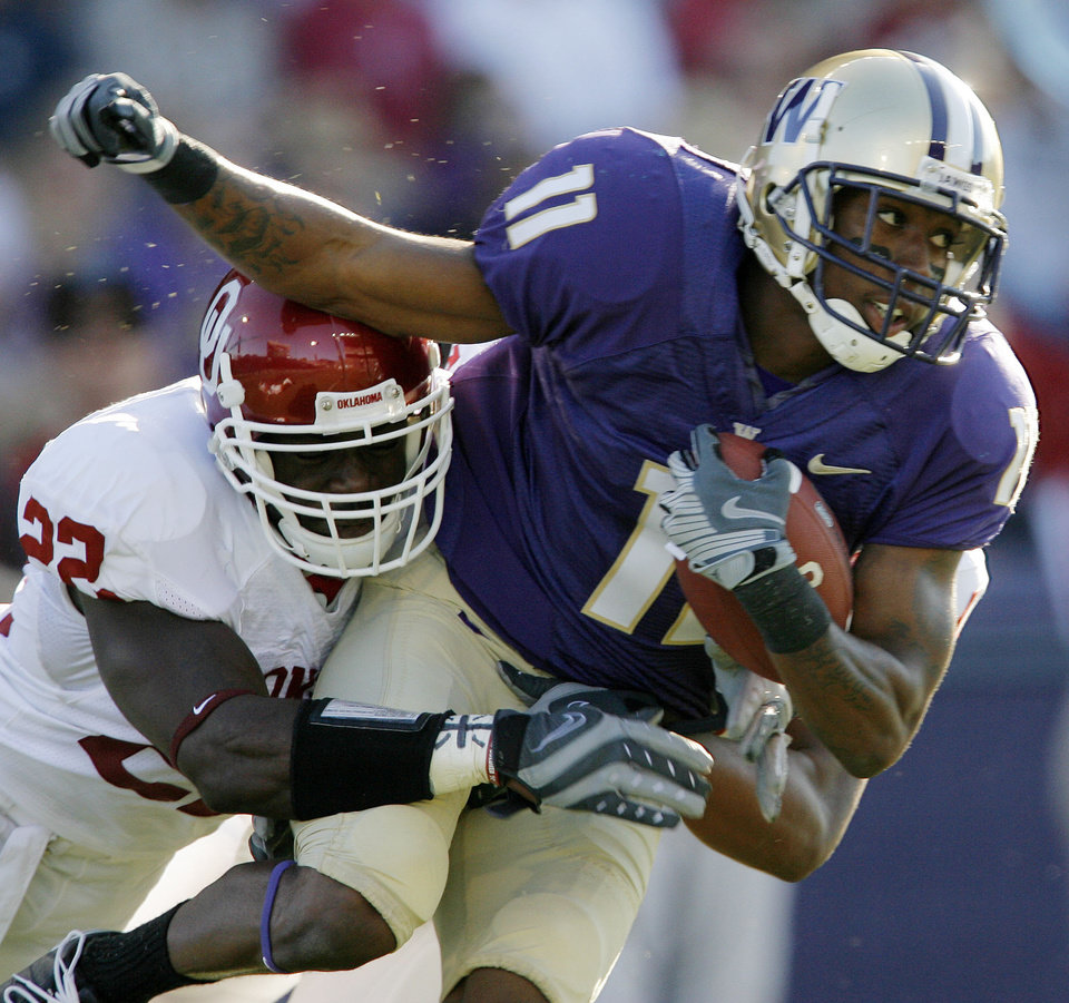 Photo - Oklahoma's Keenan Clayton (22) stops Washington's D'Andre Goodwin (11) in the first half during the college football game between Oklahoma and Washington at Husky Stadium in Seattle, Wash., Saturday, September 13, 2008. BY NATE BILLINGS, THE OKLAHOMAN