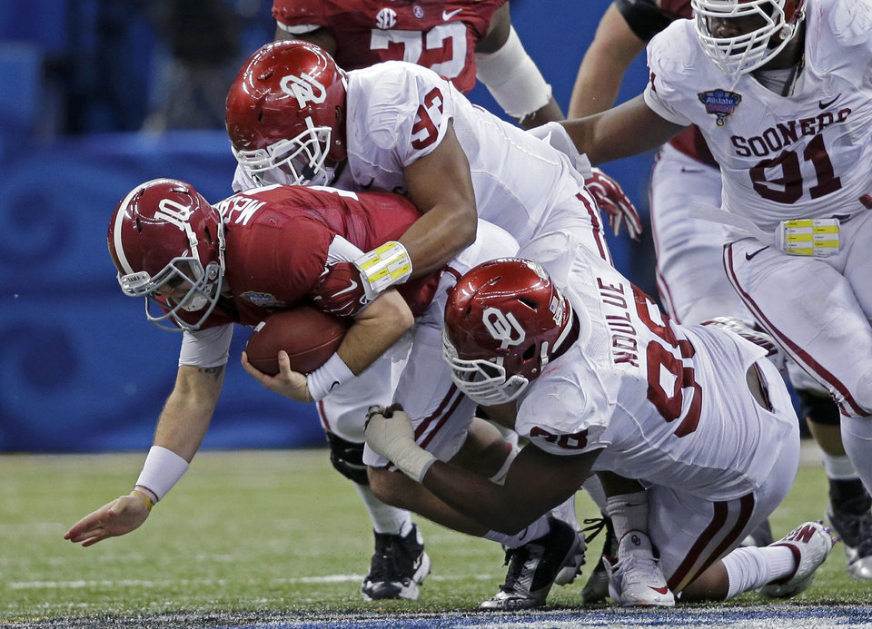 Photo -  Alabama quarterback AJ McCarron (10) is sacked by Oklahoma defensive tackles Jordan Wade (93) and  Chuka Ndulue (98) during the second half of the NCAA college football Sugar Bowl in New Orleans, Thursday, Jan. 2, 2014. (AP Photo/Patrick Semansky)