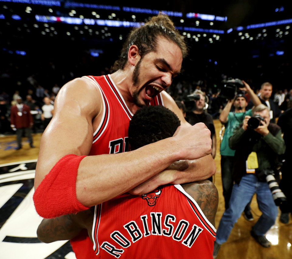 Photo - Chicago Bulls' Joakim Noah, top, celebrates with teammate Nate Robinson after defeating the Brooklyn Nets 99-93 in Game 7 of their first-round NBA basketball playoff series in New York, Saturday, May 4, 2013. The Bulls won the series to advance to a second-round series against the Miami Heat beginning Monday. (AP Photo/Julio Cortez)