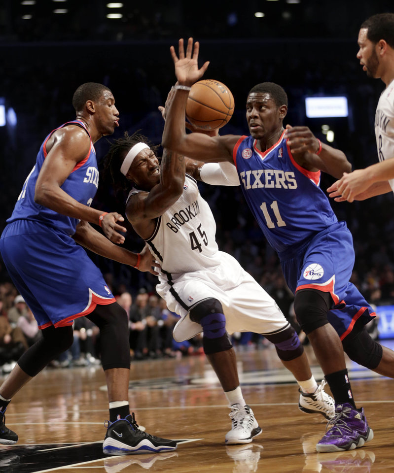 Brooklyn Nets' Gerald Wallace, second from left, is fouled by Philadelphia 76ers' Jrue Holiday (11) while Thaddeus Young, left, looks on during the first half of the NBA basketball game at the Barclays Center Sunday, Dec. 23, 2012 in New York.  (AP Photo/Seth Wenig)