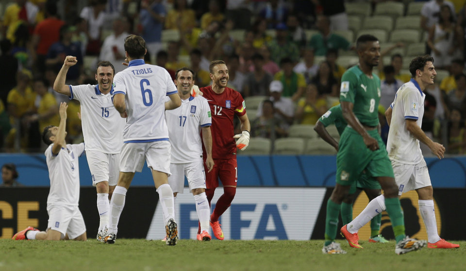 Photo - Greek players celebrate their 2-1 win after the group C World Cup soccer match between Greece and Ivory Coast at the Arena Castelao in Fortaleza, Brazil, Tuesday, June 24, 2014. (AP Photo/Natacha Pisarenko)