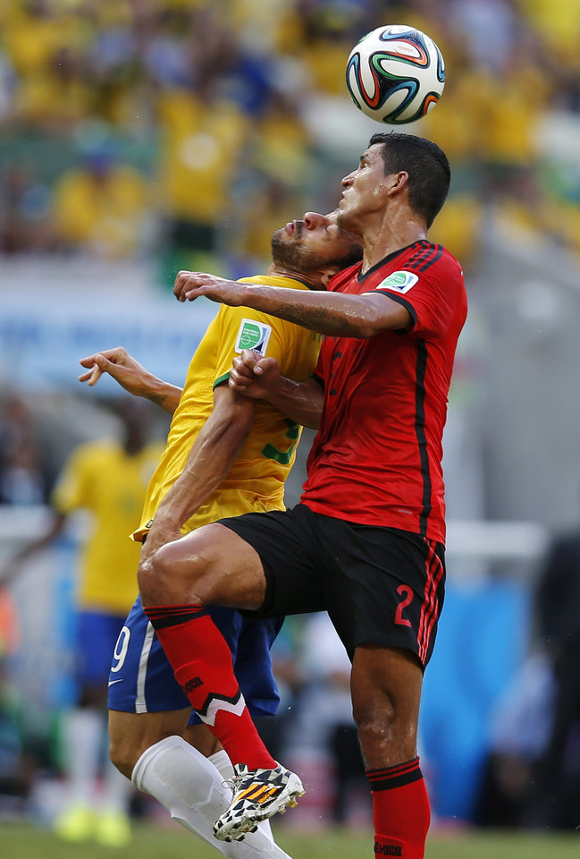 Photo - Mexico's Francisco Rodriguez, right, heads the ball against Brazil's Fred during the group A World Cup soccer match between Brazil and Mexico at the Arena Castelao in Fortaleza, Brazil, Tuesday, June 17, 2014.  (AP Photo/Eduardo Verdugo)