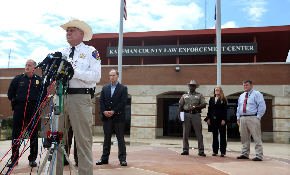 Photo - Kaufman County Sheriff David Byrnes, second from left, speaks at a news conference, Sunday, March 31, 2013, in Kaufman, Texas. On Saturday, Kaufman County District Attorney Mike McLelland and his wife, Cynthia, were murdered in their home. (AP Photo/Mike Fuentes)
