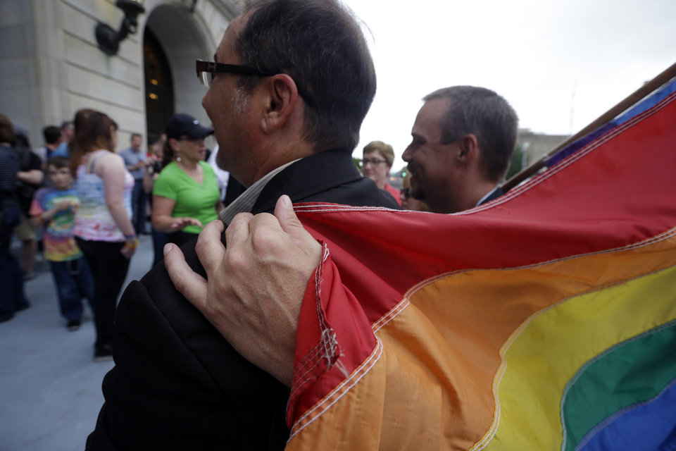 Photo - Shon DeArmon, right, puts his arm around his partner James Porter while holding a flag outside the Pulaski County Courthouse in Little Rock, Ark., Monday, May 12, 2014. The state's largest county began issuing gay marriage licenses following a judge's ruling overturning Arkansas' constitutional ban on same-sex marriage. (AP Photo/Danny Johnston)