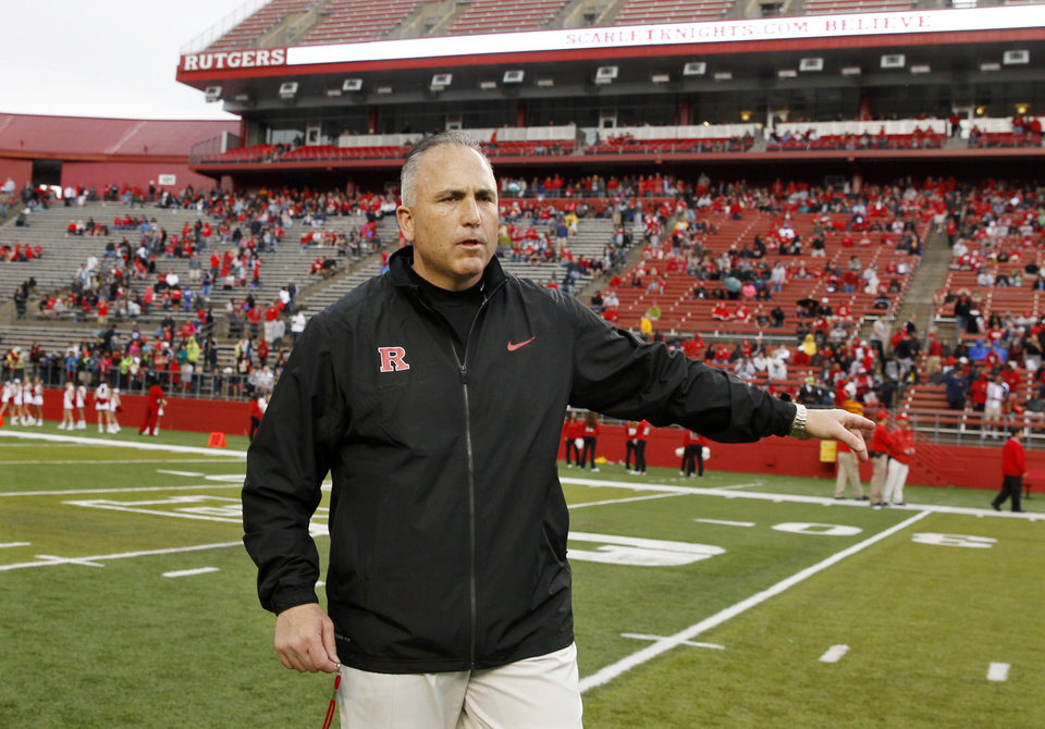 Photo - FILE - In this April 26, 2014, file photo, Rutgers head coach Kyle Flood stands on the field during their spring NCAA college football game in Piscataway, N.J. Coaches often say they are always on the hot seat. That might be true, but some seats are hotter than others. A few coaches in high-profile positions heading into 2014 very much in need of winning records and quality victories. (AP Photo/Mel Evans, File)
