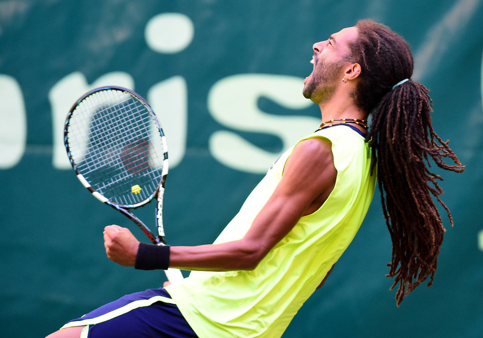 Photo - Germany's Dustin Brown celebrates after making a point against Spain's Rafael Nadal during the Gerry Weber Open tennis tournament in Halle, Germany, Thursday, June 12, 2014. Brown won the match with 6-4 and 6-1. (AP Photo/dpa, Christian Weische)