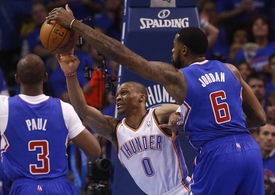 Photo - Los Angeles Clippers center DeAndre Jordan (6) blocks a pass by Oklahoma City Thunder guard Russell Westbrook (0) in the first quarter of Game 1 of the Western Conference semifinal NBA basketball playoff series in Oklahoma City, Monday, May 5, 2014. (AP Photo/Sue Ogrocki)