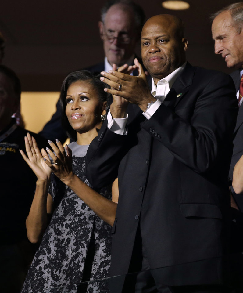 Photo - First lady Michelle Obama and her brother Craig Robinson applaud speakers during the Democratic National Convention in Charlotte, N.C., on Wednesday, Sept. 5, 2012. (AP Photo/Charlie Neibergall)  ORG XMIT: DNC179